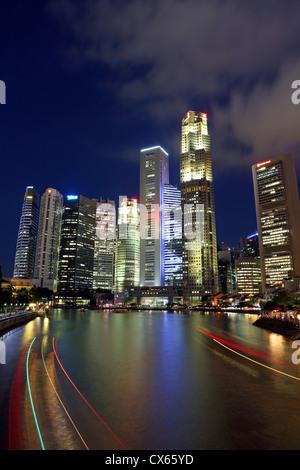 Light trails de barques sur la rivière Singapour avec des immeubles de grande hauteur du centre-ville de Singapour Banque D'Images