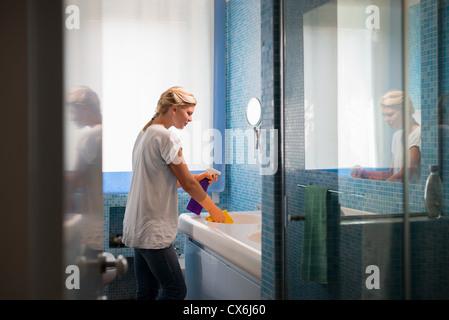 Le ménage et la vie: femme petits travaux dans salle de bains à la maison, nettoyage lavabo et robinet avec détergent Banque D'Images