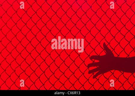 Clôture rouge et part d'ombre, concept de la liberté Banque D'Images