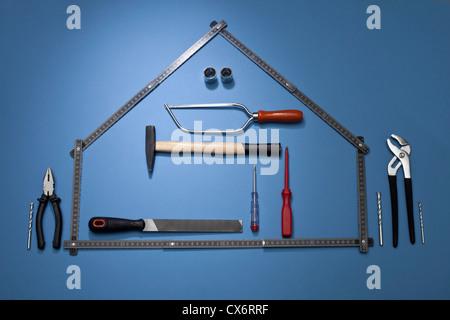 Une règle de pliage de façon à ressembler à une maison avec divers outils de travail Banque D'Images