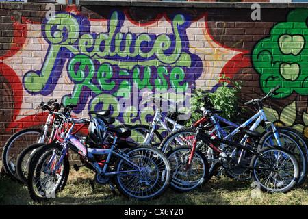 Des vélos dans une cour de récréation appuyé contre une fresque peinte sur un mur. Banque D'Images