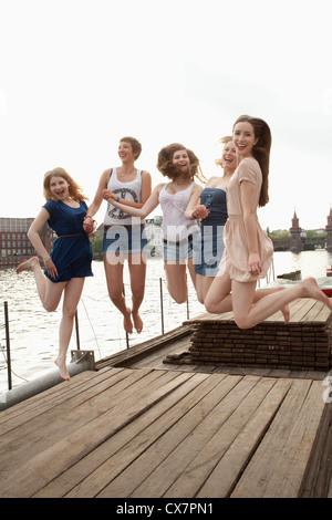 Cinq jeunes amis féminins sautant en l'air sur une jetée à côté de la Spree, Berlin, Allemagne Banque D'Images