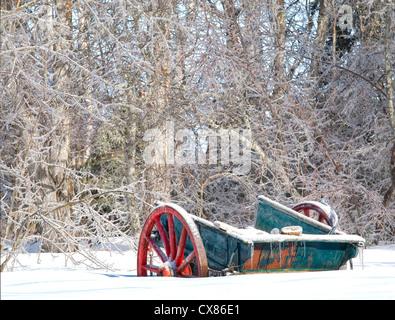 Une très vieille ferme rustique wagon à moitié enfoui dans un banc de neige. Banque D'Images