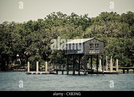 Abri à bateau et quai en bois le long de la côte et de la voie navigable avec arbres. remise à bateaux est surmonté Banque D'Images