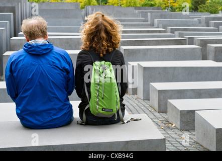 Deux touristes assis sur l'un des blocs de béton qui forment le mémorial de l'Holocauste à Berlin, Allemagne Banque D'Images