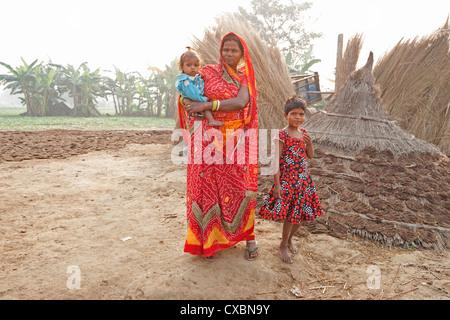 Mère en sari rouge et ses deux enfants en milieu rural à l'aube, village de Bihari Sonepur, Bihar, Inde, Asie Banque D'Images