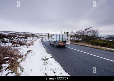 Blurred motion de Toyota Land Cruiser 4x4 voyager passé champs blancs le long de la lande route sur le froid, la Banque D'Images