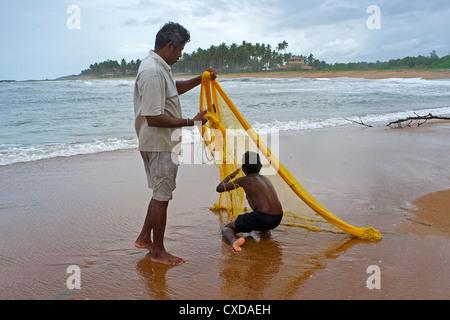 Père et fils à l'aide d'un filet de pêche lancer, près du village de Waikkal, Sri Lanka Banque D'Images