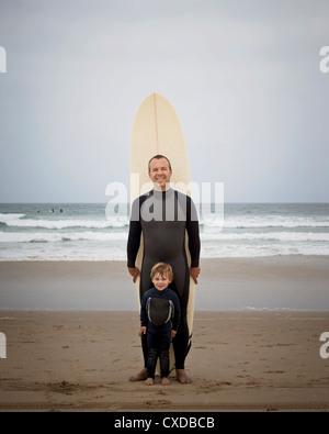 Portrait père et fils en combis with surfboard Banque D'Images