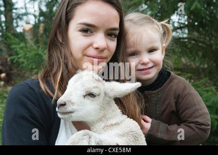Adolescente et sa petite sœur avec le pet lamb, portrait Banque D'Images