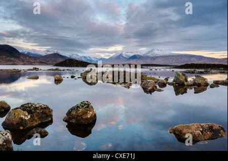 Montagnes couvertes de neige à l'aube, Lochan na h Achlaise, Rannoch Moor, Argyll and Bute, en Écosse, les Highlands Banque D'Images