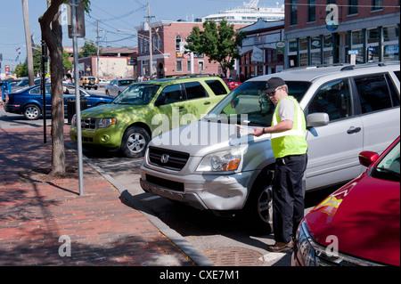 Directeur de trafic émet un billet de stationnement dans le centre-ville de Portland, Maine, USA. Banque D'Images