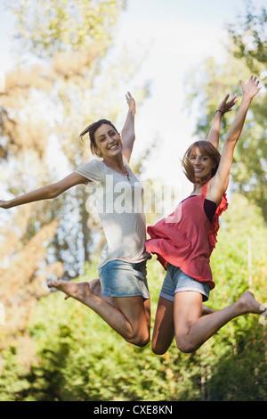 Les jeunes femmes sautant dans l'air, smiling Banque D'Images