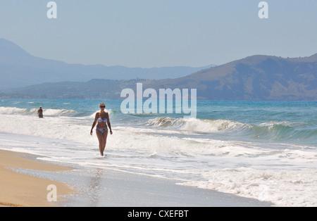 Lady marchant dans le surf le long de la plage de Paralia Kouma - à l'ouest de Rethymnon , Crète, îles grecques Banque D'Images