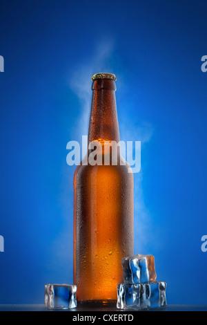 Bouteille de bière froide avec des gouttes, le gel et la vapeur sur bleu Banque D'Images