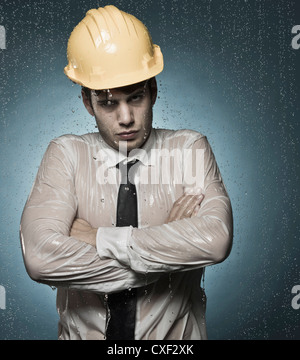 Caucasian businessman in hard-hat standing in rain