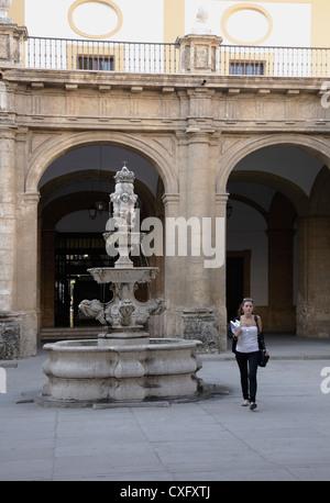 Jeune fille à la recherche d'étudiant comme marcher dans la cour intérieure de l'Université de Séville, bâtiment Banque D'Images