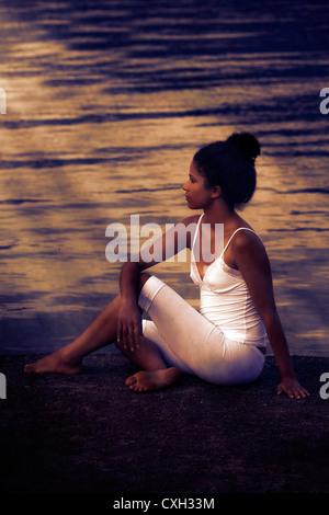 Une jeune femme est assise au bord du lac Banque D'Images
