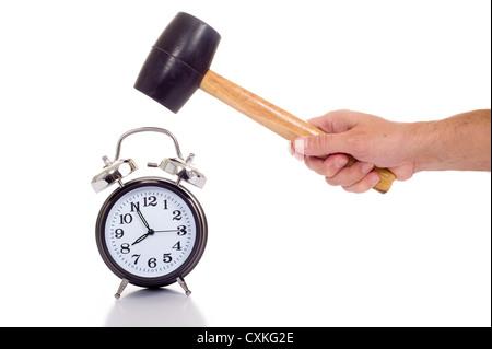 Une main tenant un marteau ou maillet noir à propos d'écraser une ancienne réveil noir sur fond blanc, concept de Banque D'Images