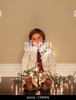 Petit garçon couvert de lumières de Noël Banque D'Images
