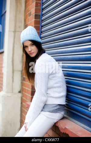 Jeune femme brune aux cheveux longs portant chapeau laineux bleu et blanc aux volets bleus contre des vêtements Banque D'Images