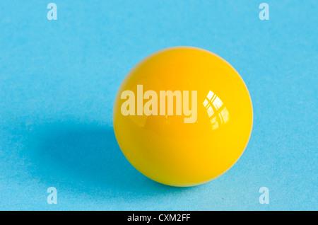Une boule de billard jaune sur fond azur avec réflexion windows Banque D'Images