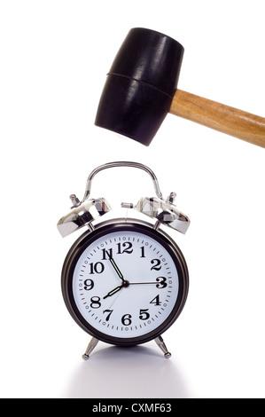 Une main tenant un marteau ou maillet noir à propos d'écraser une ancienne réveil sur un fond blanc, concept de Banque D'Images