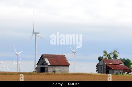 Vieux bâtiments de ferme entourée d'un parc éolien moderne Banque D'Images