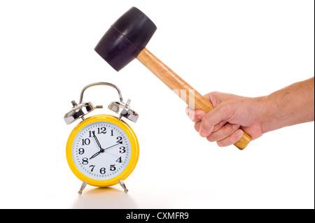 Une main tenant un marteau ou maillet noir à propos d'écraser une ancienne réveil jaune sur un fond blanc, concept Banque D'Images
