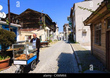 Simit vendeur dans une voie pleine de maisons traditionnelles en bois, Istanbul, Turquie Banque D'Images