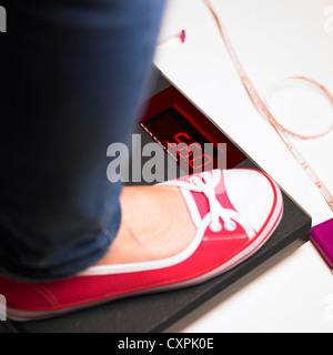 Pieds de femme sur un pèse-personne numérique avec un ruban à mesurer Banque D'Images