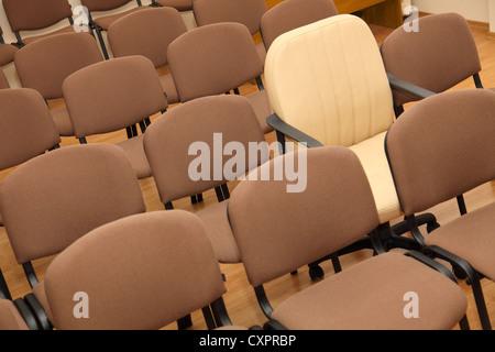 Président Manager se distingue parmi les rangées de chaises de bureau ordinaires Banque D'Images