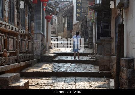 Ruelle, femme marche de larges marches de pierre entre maisons traditionnelles, des minorités Naxi, Lijiang, Yunnan, Banque D'Images