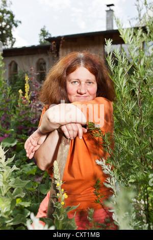 Femme s'appuyant sur des outils de jardinage Banque D'Images