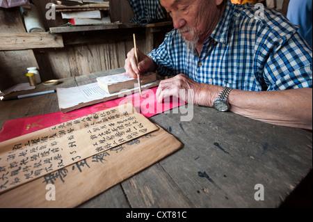 Personnes âgées chinois assis à un bureau, minorité ethnique, la pratique de la calligraphie chinoise antique, dans Banque D'Images