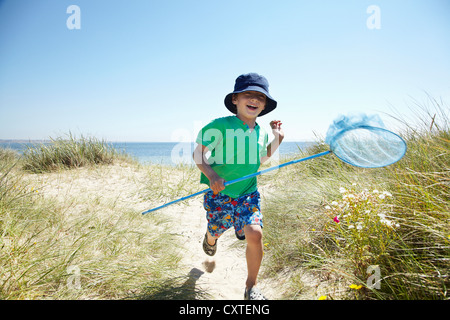 Boy carrying fishing net on beach Banque D'Images