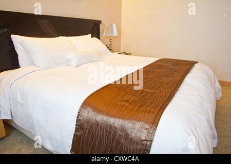 Grand lit dans une chambre d'hôtel de luxe Banque D'Images