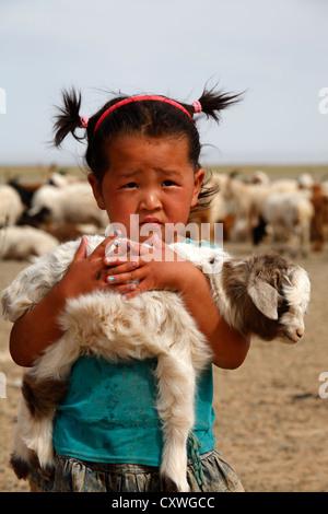 Portrait de petite fille mongole tenant un agneau dans ses bras, la Mongolie Banque D'Images