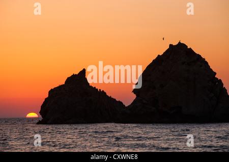 Coucher du soleil sur les rochers au large de Myrina sur Lemnos, Grèce.
