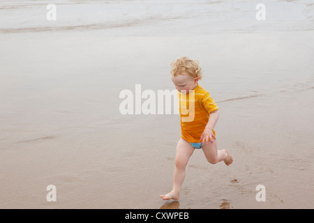 Boy running in waves on beach Banque D'Images