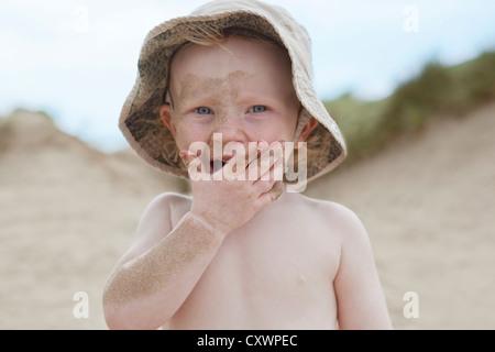 Garçon couvert de sable sur plage Banque D'Images