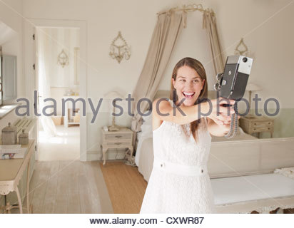 Femme à l'aide d'une caméra vidéo dans la chambre Banque D'Images