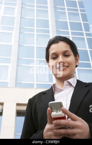 Businesswoman using cell phone Banque D'Images