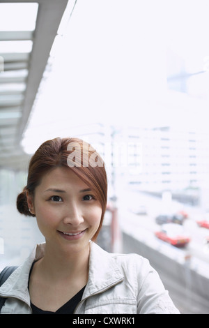 Smiling woman standing on city street Banque D'Images