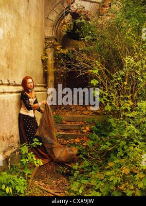 Une femme en costume d'époque, debout près du mur d'une ruine historique, et la tenue d'un long voile. Banque D'Images