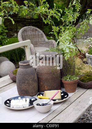 Still Life, le fromage et les olives, entourée d'accessoires de jardin décoratif sur une vieille table en bois dans un jardin romantique