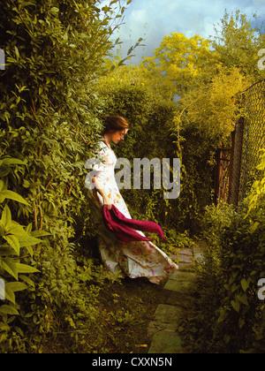 Une femme seule dans une robe blanche, avec une écharpe rouge, debout sur un chemin dans le jardin. Banque D'Images