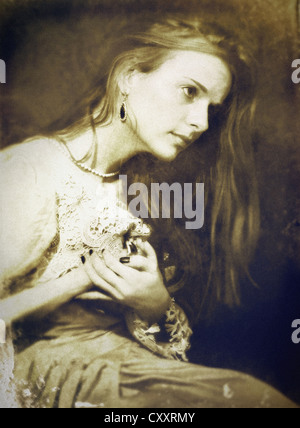 Une femme , assis, dans un costume et cheveux longs, avec l'expression douloureuse et les mains posées sur sa poitrine.