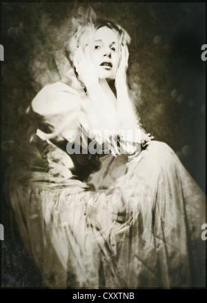 Une femme robe vintage ina, assis, avec une expression dramatique et les mains posées sur sa tête.