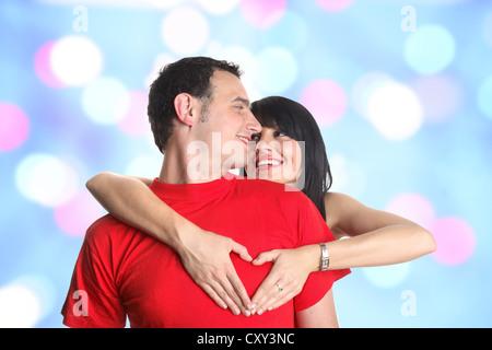 Couple et formant un geste en forme de cœur avec leurs mains Banque D'Images